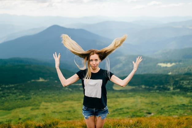 Schönes blondes junges mädchen, das oben ihr haar in den bergen wirft.