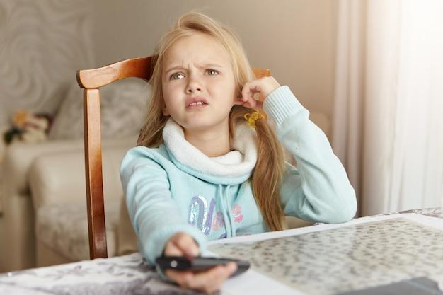 Schönes blondes kaukasisches kleines mädchen, das auf stuhl im wohnzimmer sitzt