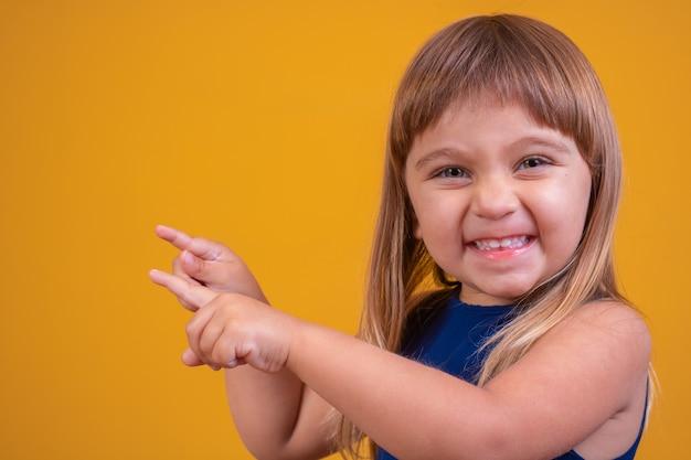 Schönes blondes kindermädchen, das die kamera betrachtet, die auf die seite zeigt.