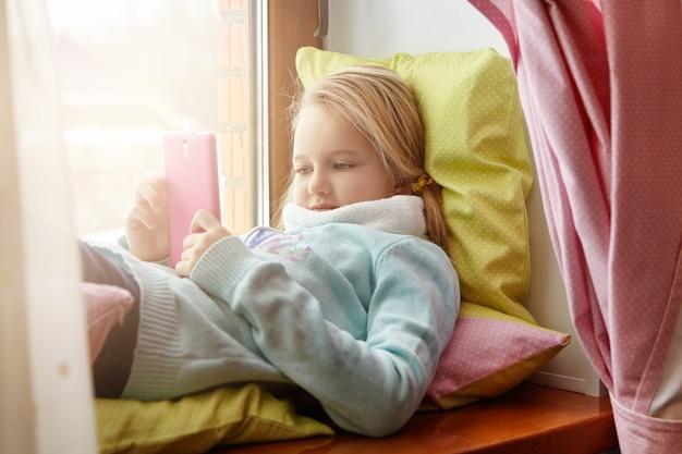 Schönes blondes kleines mädchen, das auf kissen auf fensterbank liegt und bildschirm ihres elektronischen gadgets betrachtet