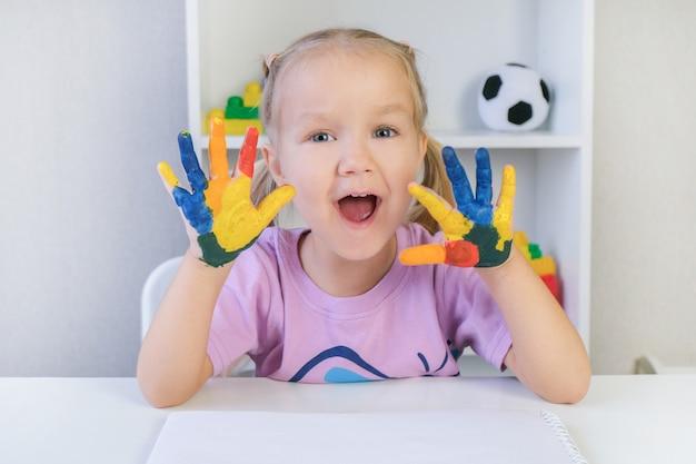 Schönes blondes kleinkindmädchen mit bunten gemalten händen, glücklich lächelnd