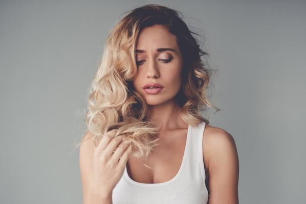 Schönes blondes mädchen berührt ihr haar.