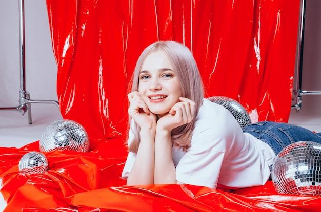 Schönes blondes mädchen, das am studio auf einem rot aufwirft