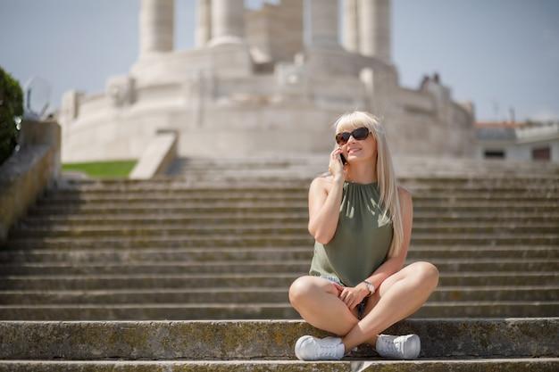 Schönes blondes mädchen, das am telefon spricht und fotos in ancona italien macht. europa italien reisen sommer