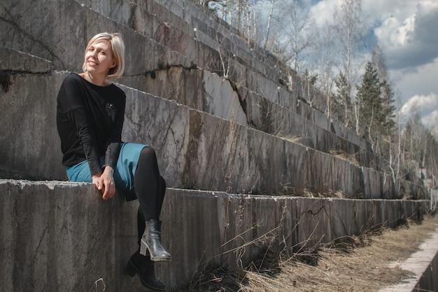 Schönes blondes mädchen, das auf einem marmortreppenhaus sitzt.