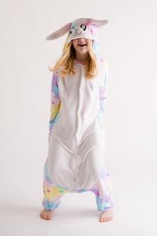Schönes blondes mädchen, das auf weiß in den kigurumi pyjamas, häschenkostüm aufwirft