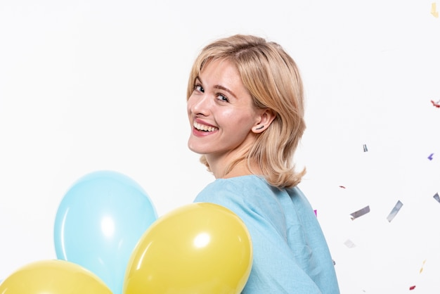 Schönes blondes mädchen, das ballone hält