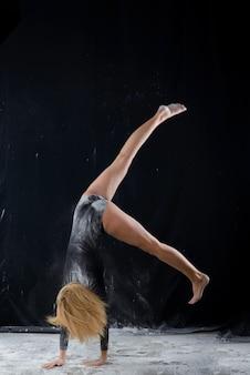 Schönes blondes mädchen, das einen schwarzen gymnastikbody trägt, der mit wolken des flugpulvers bedeckt ist