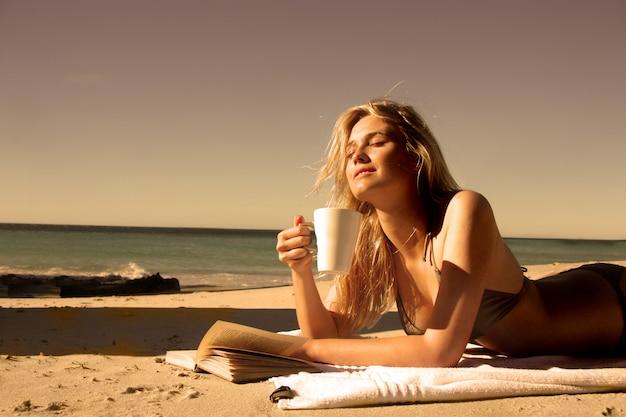 Schönes blondes mädchen, das einen tasse kaffee trinkt und ein buch auf dem strand liest