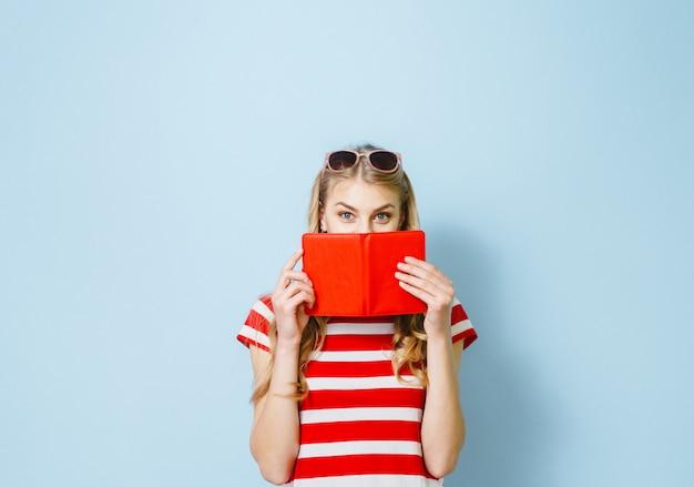 Schönes blondes mädchen, das ihre augen mit einer roten karte gegen einen blauen hintergrund versteckt