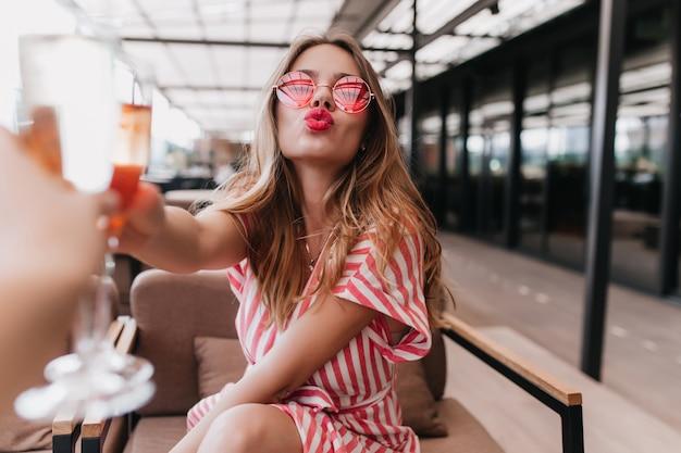 Schönes blondes mädchen, das im café mit küssendem gesichtsausdruck aufwirft. porträt der sorglosen glamourösen frau, die im sommertag chillt und cocktail genießt.