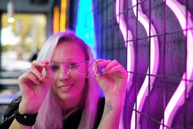 Schönes blondes mädchen, das in der bar nahe der neonwand und dem griff sitzt