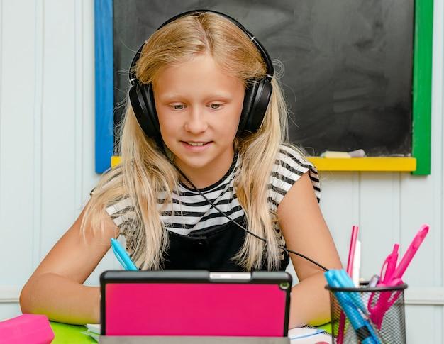 Schönes blondes mädchen, das online-englischkurs nimmt. sprachlernkonzept