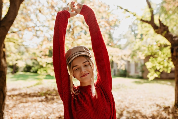 Schönes blondes mädchen fühlt sich im herbstpark glücklich. schöne junge frau im roten pullover, der zwischen blättern aufwirft.