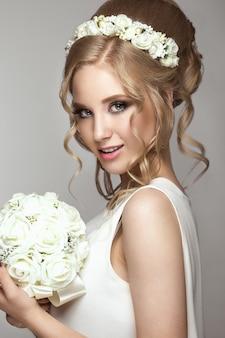 Schönes blondes mädchen im bild der braut mit weißen blumen auf ihrem kopf