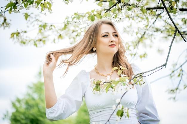 Schönes blondes mädchen im frühjahr kirschgarten.