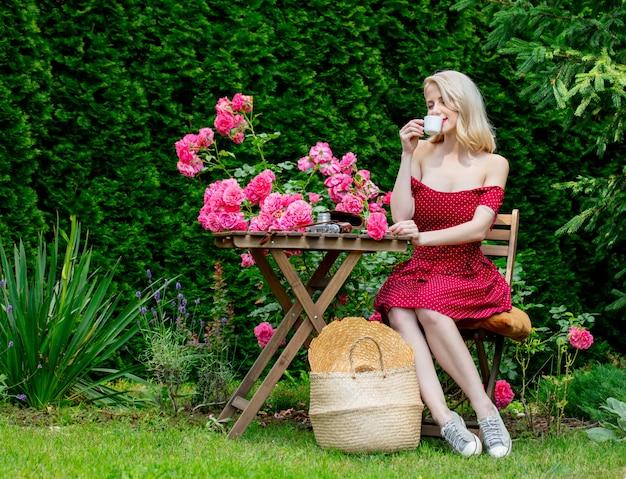 Schönes blondes mädchen im roten kleid, das einen kaffee in einem garten trinkt