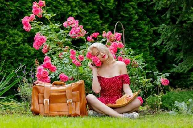 Schönes blondes mädchen im roten kleid mit koffer in einem garten