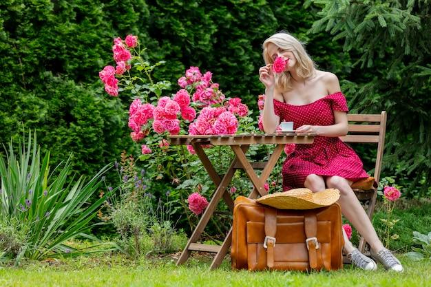 Schönes blondes mädchen im roten kleid mit koffer trinkt einen kaffee in einem garten