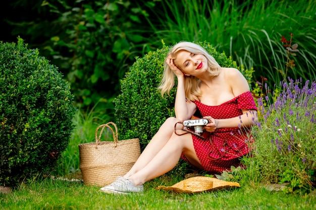Schönes blondes mädchen im roten kleid mit weinlesekamera in einem garten