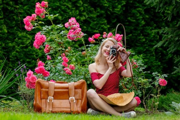 Schönes blondes mädchen im roten kleid mit weinlesekamera und koffer in einem garten