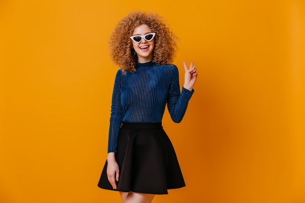 Schönes blondes mädchen in der gestreiften blauen bluse und im stilvollen rock lächelt und zeigt friedenszeichen auf gelbem raum.