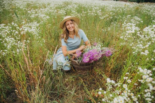 Schönes blondes mädchen in einem feld von gänseblümchen. frau in einem blauen kleid in einem feld der weißen blumen. mädchen mit einem strauß gänseblümchen. sommer zartes foto im dorf. wildblumen. mädchen in einem strohhut