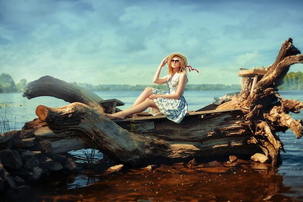 Schönes blondes mädchen in einem hut und in den gläsern, die auf treibholz am flussufer sitzen