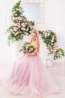 Schönes blondes mädchen in einem langen weichen lila kleid der blumen, die aufwerfen. konzept von parfums, mode und schönheit