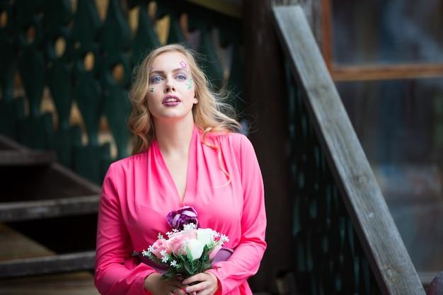 Schönes blondes mädchen in einem rosa kleid mit einem frühlingsblumenstrauß.