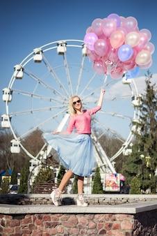 Schönes blondes mädchen in einem vergnügungspark, riesenräder mit einem großen bündel luftballons in ihren händen. rosa und blaue farben.