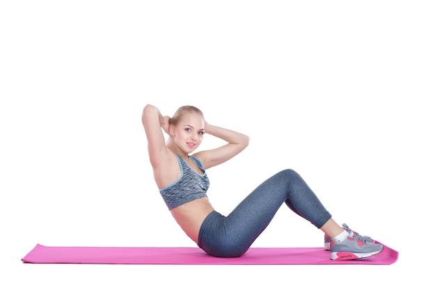 Schönes blondes mädchen in sportkleidung macht übungen auf fitnessmatte auf weißem hintergrund