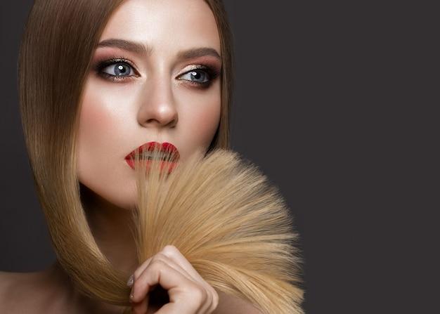 Schönes blondes mädchen mit einem tadellos glatten haar, einem klassischen make-up und roten lippen. beauty gesicht