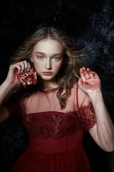 Schönes blondes mädchen mit granatapfelfrucht in den händen. frühlingsporträtmädchen in einem roten kleid, das einen granatapfel bricht