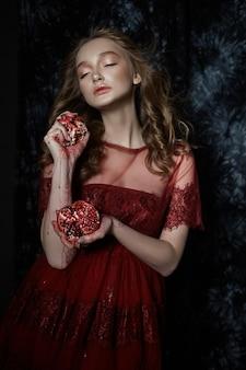 Schönes blondes mädchen mit granatapfelfrucht in ihren händen. frühlingsporträt eines mädchens in einem roten kleid, das einen granatapfel zerbricht, saft fließt über ihre hände