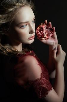 Schönes blondes mädchen mit granatapfelfrucht in ihren händen.