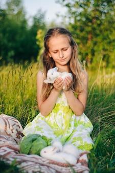 Schönes blondes mädchen mit kleinen kaninchen, die im grünen gras sitzen.
