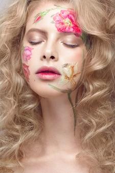 Schönes blondes mädchen mit locken und einem blumenmuster auf dem gesicht. beauty blumen.