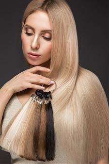 Schönes blondes mädchen mit perfekt glattem haar, klassisches make-up mit einer palette für haarverlängerungen in den händen, schönheitsgesicht,