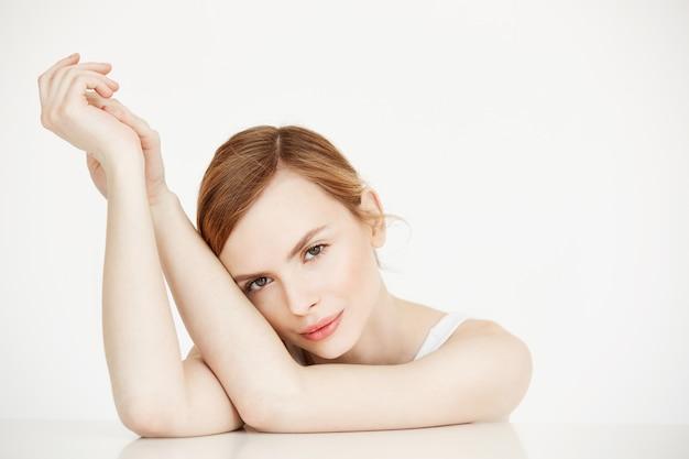 Schönes blondes mädchen mit perfekter sauberer haut lächelnd am tisch sitzen. kosmetologie. gesichtsbehandlung.