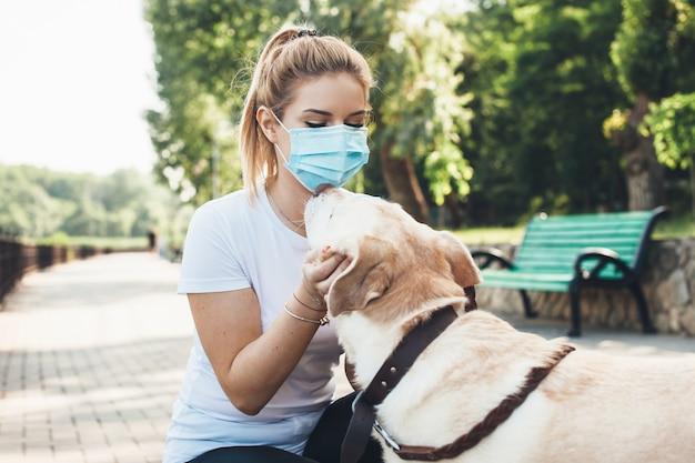 Schönes blondes mädchen und ihr labrador umarmen sich in einem park, während sie eine medizinische maske tragen