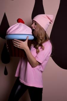 Schönes blondes modell mit gewelltem haar in rosafarbener mütze, das einen großen cupcake auf rosafarbenem hintergrund beißt. urlaubskonzept
