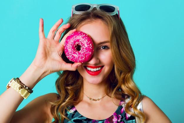 Schönes blondes modemodellmädchen, das bunte rosa donuts nimmt. lustige freudige frau mit süßigkeiten, nachtisch. diät, diätkonzept. junk food. helle farben.
