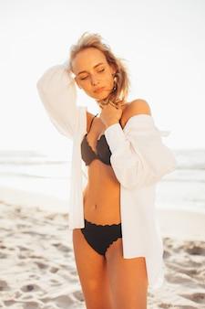 Schönes blondes schlankes mädchen in einem schwarzen bikini am strand des ozeans gegen die sonne mit ihren geschlossenen augen