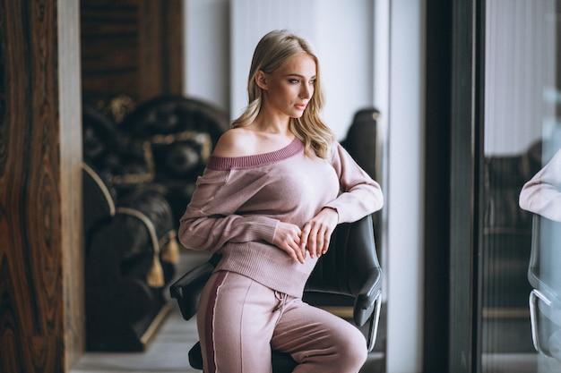 Schönes blondes sitzen auf stuhl