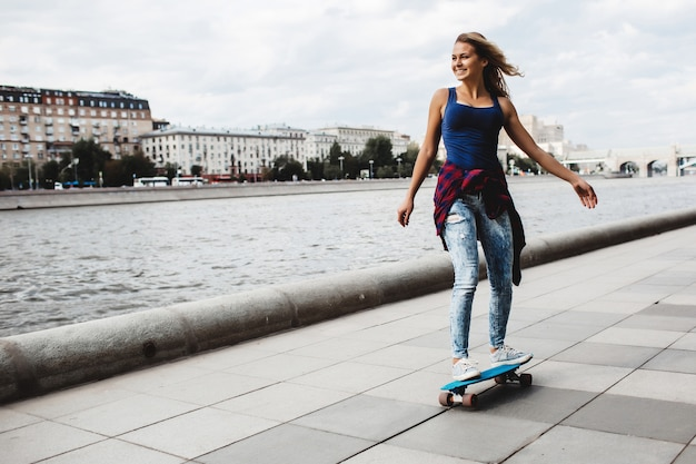 Schönes blondes skateboard auf der promenade