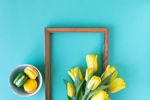 Schönes blumenarrangement. gelbe blumen tulpen, leerer rahmen für text auf blauem hintergrund. hochzeit. geburtstag valentinstag. muttertag. flache lage, draufsicht, kopierraum