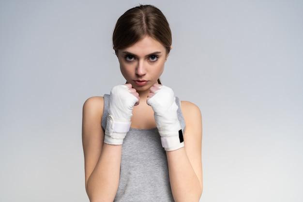 Schönes boxermädchen, das sportliche kleidung und handschuhe trägt, die im studio über grau üben.