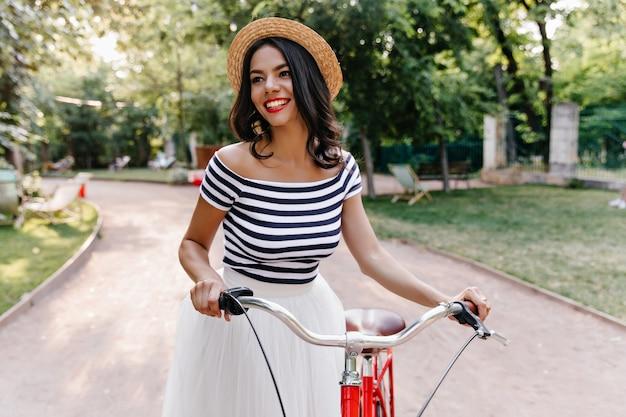 Schönes braunhaariges mädchen, das naturansichten während des spaziergangs genießt. außenaufnahme der prächtigen lateinischen frau im hut, der mit fahrrad im park aufwirft.