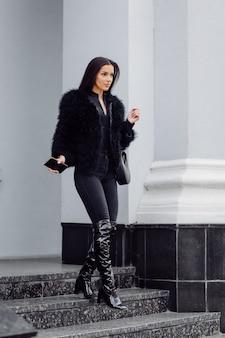 Schönes braunhaariges stilvolles mädchen im schwarzen kleid im freien. junges attraktives elegantes frauenporträt mit langen haaren am frühling in den stadtstraßen.